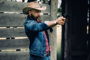 Bearded cowboy with a gun.