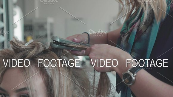 Woman Hairdresser Making Curls At Blond Hair With Curling Irons