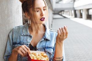 Portrait of happy young woman eating popcorn
