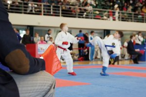 Martial art competitions - coach-judge with red flag looking at karate teenager's fighting