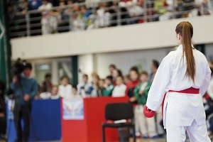Sports kids - teenager girl sportsmen on karate at tatami arena - ready for fight