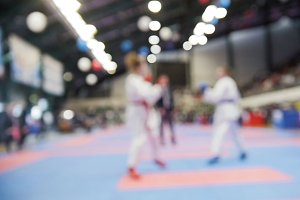 Teenagers karatekas fight on karate competitions, de-focused sport background