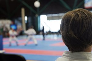 Karate competition - teenager boys looking at fighting on tatami arena