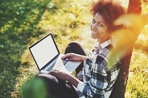 Cute curly girl in park with laptop