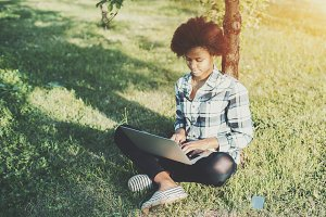 Black female with laptop on grass