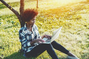 Black girl on meadow with laptop