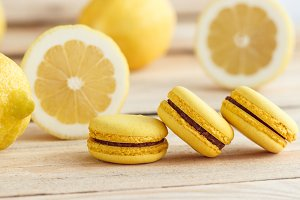 Yellow french macarons with lemons on the wooden boards