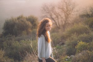 beautiful young girl smiling at sunset