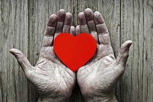 Paper heart in the hands of an elder