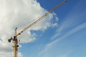 Yellow construction crane in front of blue sky - construction site
