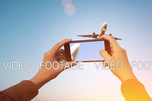Looped cinematograph of hand holding smartphone while recording video of landing airplanes