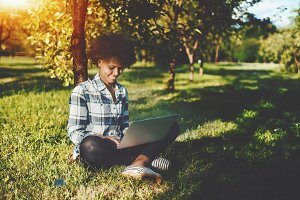 Black girl with laptop on grass
