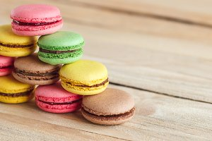Green, pink, yellow and brown french macarons on the wooden boards