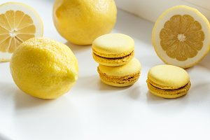 Yellow french macarons with lemons on the table