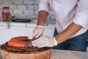 Chef cutting salmon