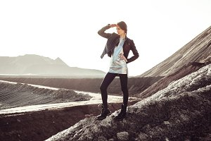 Beautiful fashion young woman climbing into mountains