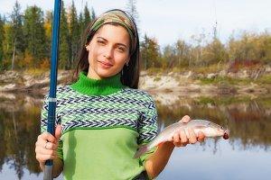 Beautiful girl at the autumn fishing