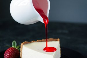 Pouring sauce over cheesecake