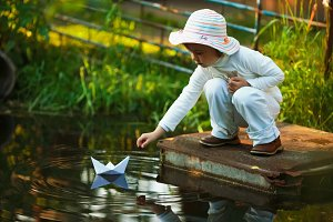 girl plays with paper boat in the river