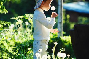 girl with dandelion in summer park