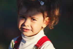 little girl with sun rays on face