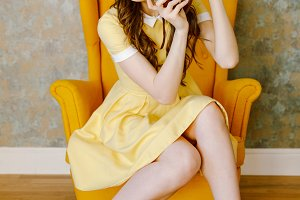 Pretty young pin up woman in dress sitting in chair