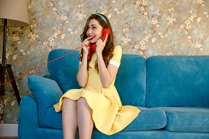 Happy young pin-up lady talking by phone.