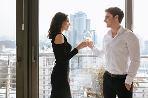 Happy loving couple standing near window drinking alcohol