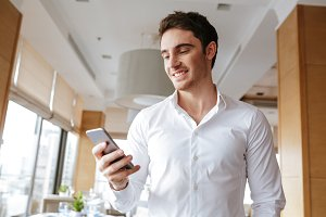 Handsome happy young man standing in cafe chatting by phone.