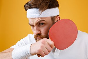 Handsome young sportsman holding racket for table tennis.
