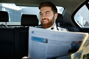 Happy bearded man sitting with newspaper