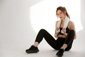 Concentrated sports woman sitting with towel