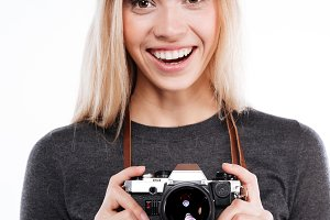 Smiling woman in casual clothes standing and holding retro camera