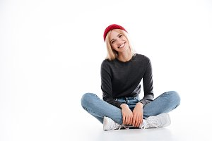 Smiling female hipster sitting on the floor