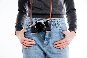Woman in jeans with retro camera holding hands in pockets