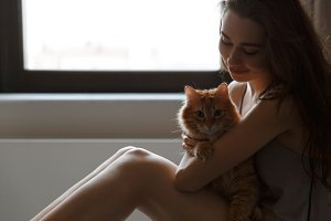 Cropped image of woman in nightie with cat