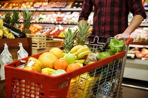 Man with shopping trolley choosing fruits in supermarket