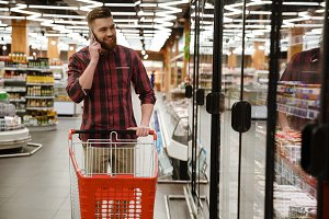 Happy young man standing in supermarket talking by phone
