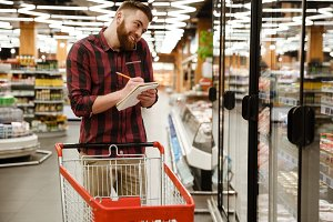 Cheerful young man in supermarket talking by phone writing notes