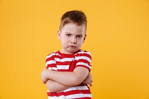 Portrait of a frowning upset little boy looking at camera