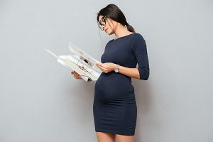 Concentrated pregnant business woman reading documents