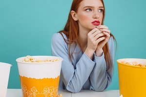 Vertical image of Pensive woman eating popcorn