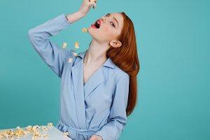 Vertical image of ginger woman eating popcorn