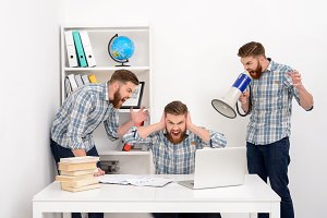 Businessman working with multiple clones of himself at the office