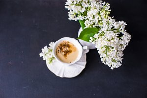 Cup of coffee and white lilac