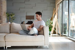 Young man using laptop while sitting in living room