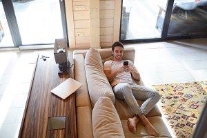Man with phone lying on sofa