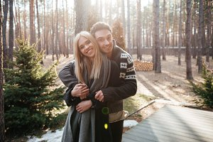 Happy loving couple standing outdoors in the forest