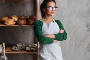 Concentrated young lady baker standing with arms crossed