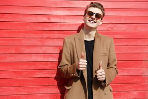 Happy young man in sunglasses standing and showing thumbs up
